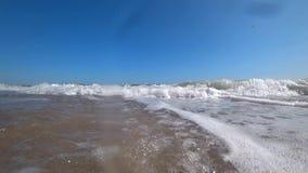Τα ωκεάνια κύματα καλύπτουν μια κάμερα σε μια όμορφη αμμώδη παραλία μια ηλιόλουστη θερινή ημέρα απόθεμα βίντεο