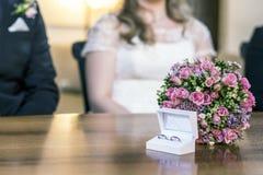 Τα όμορφα γαμήλια δαχτυλίδια βρίσκονται στην ξύλινη επιφάνεια στα πλαίσια μιας ανθοδέσμης των λουλουδιών και του γαμήλιου ζεύγους Στοκ Φωτογραφία