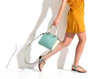 Τα όμορφα θηλυκά πόδια που φορούν τα θερινά παπούτσια στους καφετιούς κίτρινους σχεδιαστές ντύνουν και μπλε τσάντα συμπλεκτών γυν Στοκ Εικόνα