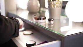 Τα όμορφα θηλυκά χέρια με ένα κόκκινο μανικιούρ παίρνουν έξω τα καλλυντικά για το makeup από το γλείψιμο: μια σκόνη, μάτι σκιάζει απόθεμα βίντεο
