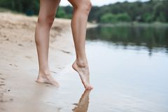 Τα όμορφα θηλυκά πόδια πηγαίνουν στο νερό Ποταμός Στοκ Εικόνες