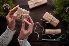 Τα όμορφα θηλυκά χέρια είναι συσκευασμένο δώρο Χριστουγέννων στο καφετί έγγραφο του Κραφτ Στοκ φωτογραφία με δικαίωμα ελεύθερης χρήσης