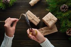 Τα όμορφα θηλυκά χέρια με το ψαλίδι κόβουν το σχοινί, δώρα Χριστουγέννων στο καφετί έγγραφο του Κραφτ Στοκ φωτογραφία με δικαίωμα ελεύθερης χρήσης