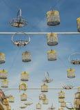 Τα όμορφα και ζωηρόχρωμα κλουβιά πουλιών κρέμασαν τη μέση των κτηρίων Στοκ Φωτογραφίες