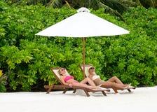 Τα όμορφα κορίτσια που χαλαρώνουν σε μια παραλία προεδρεύουν πλησίον Στοκ φωτογραφία με δικαίωμα ελεύθερης χρήσης