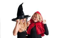 Τα όμορφα κορίτσια στο κοστούμι αποκριών μαγεύουν και λίγη κόκκινη οδηγώντας κουκούλα Στοκ Εικόνες
