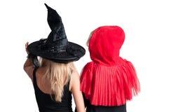 Τα όμορφα κορίτσια στο κοστούμι αποκριών μαγεύουν και λίγη κόκκινη οδηγώντας κουκούλα Στοκ Φωτογραφίες