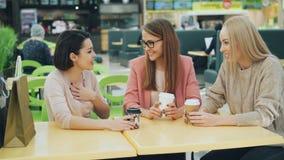 Τα όμορφα κορίτσια ψήνουν και τα γυαλιά με τα ποτά καθμένος στον καφέ στη λεωφόρο αγορών κουβεντιάζοντας έπειτα και απόθεμα βίντεο