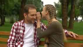 Τα όμορφα μυστικά ψιθυρίσματος έφηβη κόρη στον πατέρα, χαλαρώνουν στον πάγκο στο πάρκο απόθεμα βίντεο
