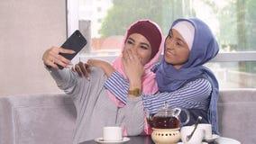 Τα όμορφα νέα μουσουλμανικά κορίτσια selfie σε ένα smartphone Στοκ Εικόνες