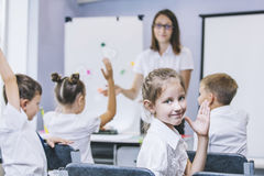 Τα όμορφα παιδιά είναι σπουδαστές μαζί σε μια τάξη στο schoo στοκ εικόνες