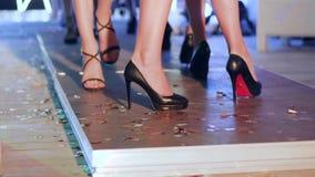 Τα όμορφα πόδια των προτύπων στα μαύρα υποδήματα πηγαίνουν κατά μήκος του στενού διαδρόμου στη επίδειξη μόδας φιλμ μικρού μήκους