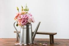 Τα όμορφα ρόδινα λουλούδια στο πότισμα μπορούν και μικρός ξύλινος πάγκος στην επιτραπέζια κορυφή Στοκ εικόνα με δικαίωμα ελεύθερης χρήσης