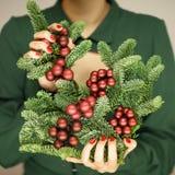 Τα όμορφα χέρια γυναικών με το κόκκινο καρφί γυαλίζουν τον κλάδο πεύκων εκμετάλλευσης με τις διακοσμήσεις Χριστουγέννων στοκ φωτογραφία με δικαίωμα ελεύθερης χρήσης