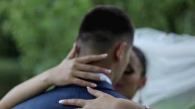 Τα όμορφα newlyweds αγκαλιάζουν ήπια συνδέστε τις νεολαίες αγάπης αγάπη τρυφερότητας φιλμ μικρού μήκους