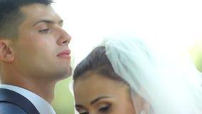 Τα όμορφα newlyweds αγκαλιάζουν ήπια συνδέστε τις νεολαίες αγάπης ευτυχής εκλεκτής ποιότητας γάμος ημέρας ζευγών ιματισμού απόθεμα βίντεο
