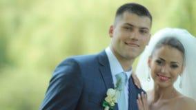 Τα όμορφα newlyweds αγκαλιάζουν ήπια συνδέστε τις νεολαίες αγάπης ευτυχής εκλεκτής ποιότητας γάμος ημέρας ζευγών ιματισμού φιλμ μικρού μήκους