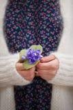 Τα όμορφα snowdrops στα χέρια μιας νέας γυναίκας στην άσπρα ζακέτα και το λουλούδι μπλε ντύνουν Στοκ Φωτογραφίες