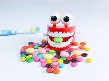 Τα δόντια χλευάζουν επάνω με την οδοντόβουρτσα και τις ζωηρόχρωμες καραμέλες Στοκ Εικόνες
