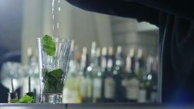 Τα όπλα του barkeeper προσθέτουν το φρέσκο χυμό στο διαφανές ποτήρι με την κινηματογράφηση σε πρώτο πλάνο μεντών πρασινάδων και α φιλμ μικρού μήκους