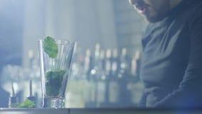 Τα όπλα bartender με το βραχιόλι ρίχνουν στη διαφανή κινηματογράφηση σε πρώτο πλάνο φύλλων μεντών γυαλιού και φετών ασβέστη απόθεμα βίντεο