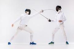 Τα δύο άτομα που φορούν την άσκηση κοστουμιών περίφραξης με το ξίφος ενάντια σε γκρίζο Στοκ Φωτογραφία