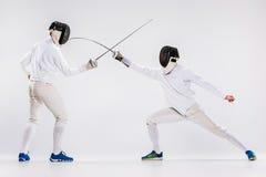 Τα δύο άτομα που φορούν την άσκηση κοστουμιών περίφραξης με το ξίφος ενάντια σε γκρίζο Στοκ Φωτογραφίες