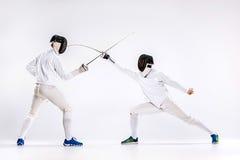 Τα δύο άτομα που φορούν την άσκηση κοστουμιών περίφραξης με το ξίφος ενάντια σε γκρίζο Στοκ φωτογραφίες με δικαίωμα ελεύθερης χρήσης