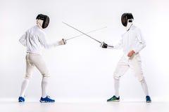 Τα δύο άτομα που φορούν την άσκηση κοστουμιών περίφραξης με το ξίφος ενάντια σε γκρίζο Στοκ εικόνες με δικαίωμα ελεύθερης χρήσης