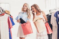 Τα δύο νέα όμορφα κορίτσια που εξετάζουν τα φορέματα και προσπαθούν σε το επιλέγοντας στο κατάστημα στοκ εικόνες με δικαίωμα ελεύθερης χρήσης