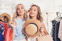 Τα δύο νέα όμορφα κορίτσια που εξετάζουν τα φορέματα και προσπαθούν σε το επιλέγοντας στο κατάστημα στοκ φωτογραφία