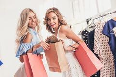 Τα δύο νέα όμορφα κορίτσια που εξετάζουν τα φορέματα και προσπαθούν σε το επιλέγοντας στο κατάστημα στοκ εικόνα