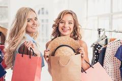 Τα δύο νέα όμορφα κορίτσια που εξετάζουν τα φορέματα και προσπαθούν σε το επιλέγοντας στο κατάστημα στοκ εικόνες
