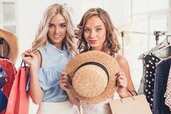 Τα δύο νέα όμορφα κορίτσια που εξετάζουν τα φορέματα και προσπαθούν σε το επιλέγοντας στο κατάστημα στοκ φωτογραφίες με δικαίωμα ελεύθερης χρήσης