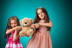Τα δύο χαριτωμένα μικρά κορίτσια στο μπλε υπόβαθρο με Teddy αντέχουν Στοκ Εικόνα