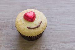 Τα cupcakes με την καρδιά διαμορφώνουν τη σοκολάτα στον ξύλινο πίνακα Στοκ Εικόνες