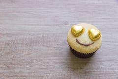 Τα cupcakes με την καρδιά διαμορφώνουν τη σοκολάτα στον ξύλινο πίνακα Στοκ φωτογραφία με δικαίωμα ελεύθερης χρήσης