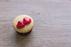 Τα cupcakes με την καρδιά διαμορφώνουν τη σοκολάτα στον ξύλινο πίνακα Στοκ εικόνες με δικαίωμα ελεύθερης χρήσης
