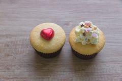 Τα cupcakes με την καρδιά διαμορφώνουν τη σοκολάτα στον ξύλινο πίνακα Στοκ εικόνα με δικαίωμα ελεύθερης χρήσης