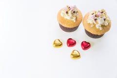 Τα cupcakes με την καρδιά διαμορφώνουν τη σοκολάτα στον ξύλινο πίνακα Στοκ Φωτογραφία
