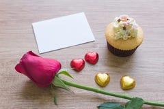 Τα cupcakes με την καρδιά διαμορφώνουν τη σοκολάτα στον ξύλινο πίνακα Στοκ Φωτογραφίες