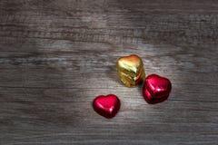 Τα cupcakes με την καρδιά διαμορφώνουν τη σοκολάτα στον ξύλινο πίνακα Στοκ Εικόνα