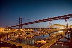Τα 25 de Abril Bridge και θαλάσσιο βράδυ Στοκ Φωτογραφία