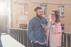 Τα hipsters νέων περπατούν και μιλούν στο τηλέφωνο κυττάρων Το νέο γενειοφόρο άτομο στέκεται και χαμογελά στοκ φωτογραφίες