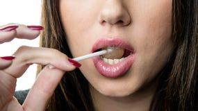 Τα Juicy μεγάλα χείλια μιας γυναίκας δαγκώνουν ένα lollipop Στοκ φωτογραφίες με δικαίωμα ελεύθερης χρήσης