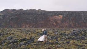 Τα newlyweds αγκαλιάζουν στη φύση φιλμ μικρού μήκους