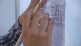 Τα Unrecognizable χέρια αρχιτεκτόνων που λειτουργούν με το σκίτσο, σχέδιο, προγραμματίζουν κοντά στο φωτεινό καθαρό γραφείο το πα φιλμ μικρού μήκους