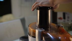 Τεθειμένα καρότα σε ένα juicer ηλεκτρονικός εξολκέας χυμού στην κουζίνα απόθεμα βίντεο