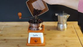 Τεθειμένα φασόλια καφέ στο χειρωνακτικό μύλο καφέ απόθεμα βίντεο