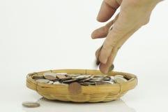 τεθειμένα χέρι νομίσματα στο καλάθι Στοκ Φωτογραφίες